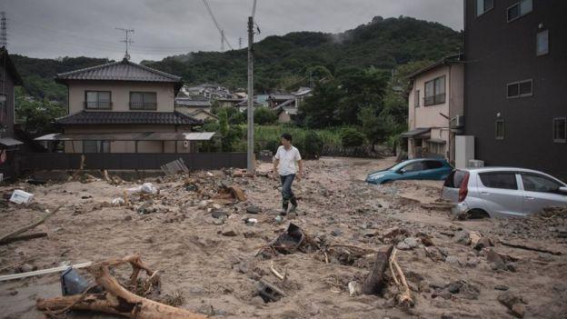 Man walks past a devastated street during floods in Saka