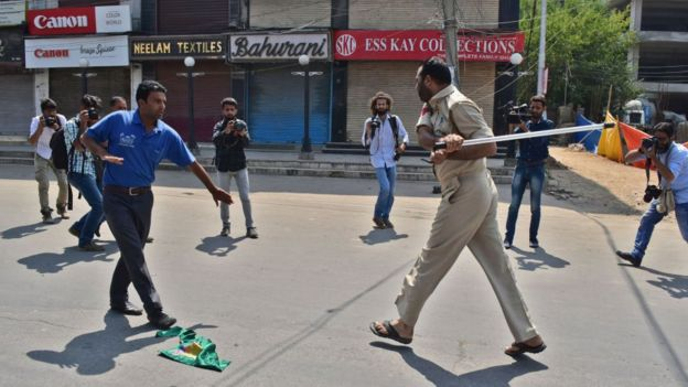 A police officer tries striking a Kashmir Shiite mourner during the procession. Authorities in parts of Srinagar imposed strict restrictions to prevent Shiite Muslims from taking part in Muharram procession.