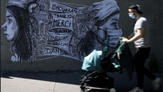 Man walks in mask and with stroller in front of mural in France