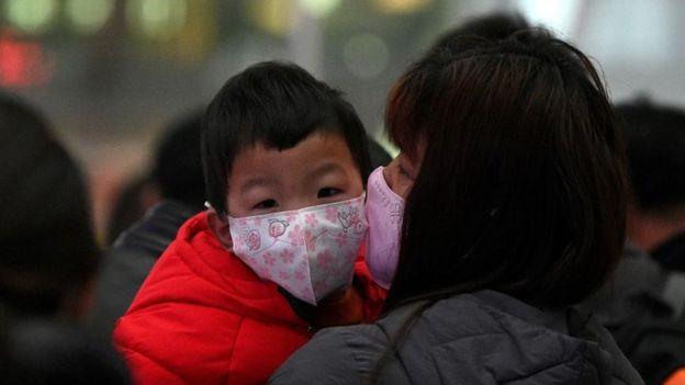 Mujer con un niño en sus brazos, ambos con mascarilla.