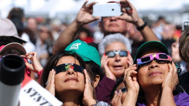 People look through eclipse viewing glasses, telescopes or photo cameras on the Indian Ocean island of La Reunion.