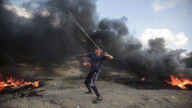 A Palestinian protester takes part during the clashes with Israeli troops near the border with Israel in the east of Gaza City on, 20 July 2018.