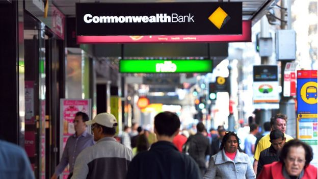 People on the street under Commonwealth Bank sign.