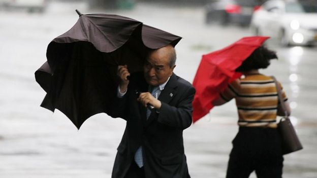 A man struggles with an umbrella as Typhoon Lingling approaches in Seoul, South Korea, 7 September 2019