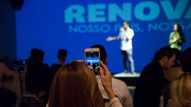 Mulher tira foto de palestra do RenovaBR