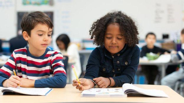 Dos niños de aspecto muy diferentes hacen la tarea en la escuela.