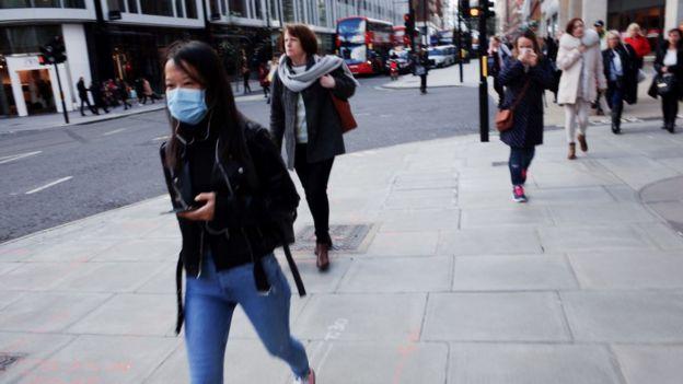 Pessoas andando numa calçada, algumas com mascara