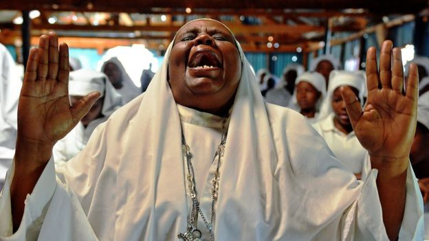 A woman praying in church in Kenya - archive shot