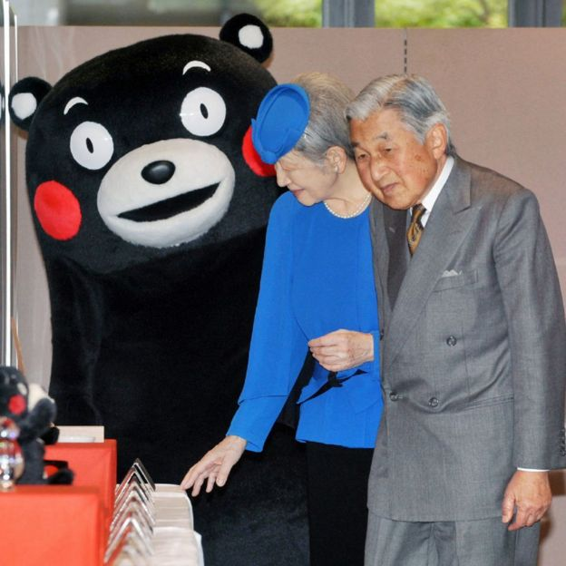 Japanese Emperor Akihito (R) and Empress Michiko (C) stand next to 'Kumamon' (L)