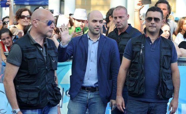 Roberto Saviano mühafizəçilərlə 2013-cü ildə kino festivalında