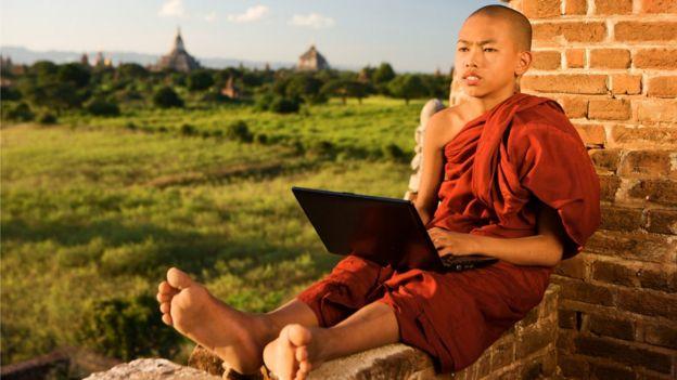 Monje budista con una computadora.