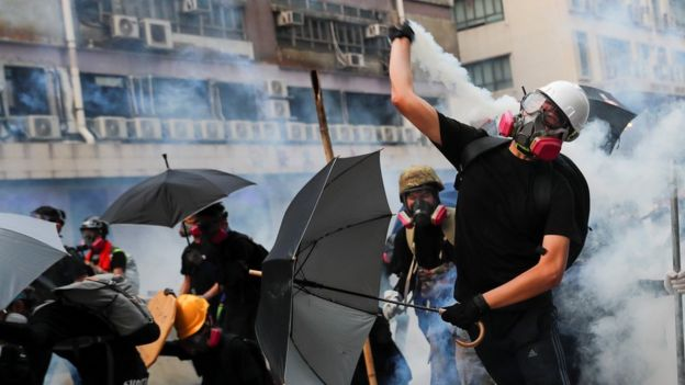 A demonstrator throws back a tear gas canister as they clash with riot police during a protest in Hong Kong, China, August 24, 2019.