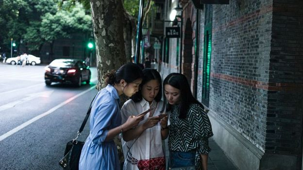 Women look at their smartphones in Xintiandi district, a shopping area, in Shanghai on September 8, 2016.