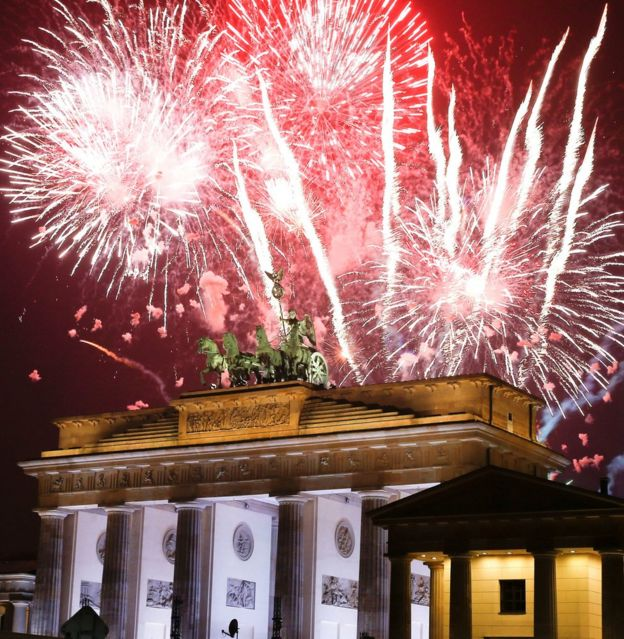 fireworks explode next to the quadriga sculpture atop the brandenburg gate during new year celebrations in