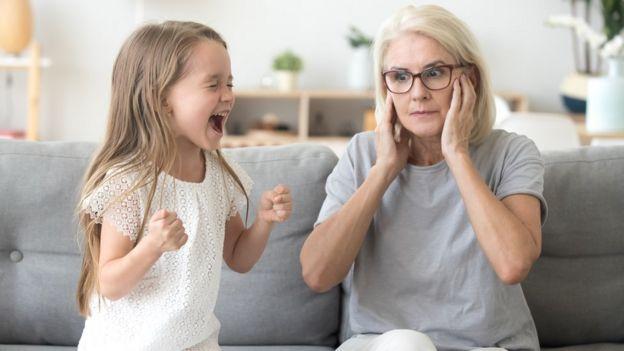 Niña gritando y señora cubriendo sus oídos