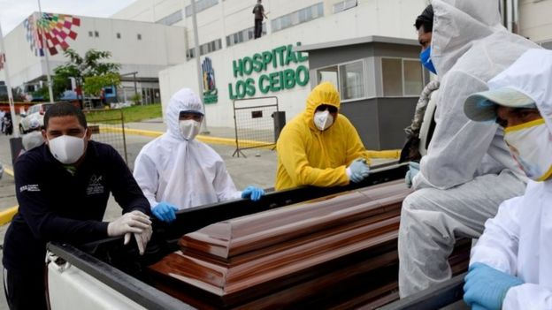 Mortuary workers carry a coffin
