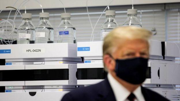Trump de máscara em laboratório, olhando para o lado