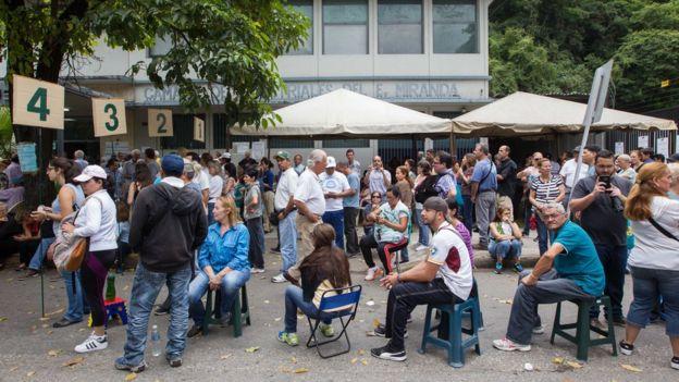 Filas de votantes ante un centro de votación.