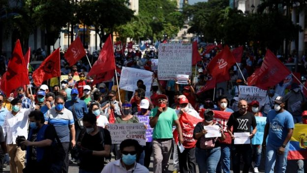 Protesters holding flags and banners march in Guayaquil
