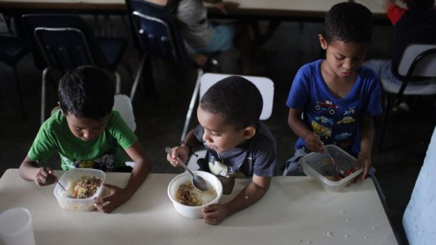 Children eat lunch at Madre Asuncion's community kitchen on October 9, 2019 in Petare, Caracas, Venezuela.