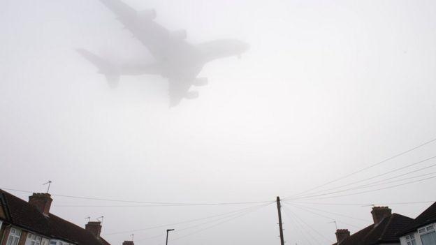 A plane flies through fog