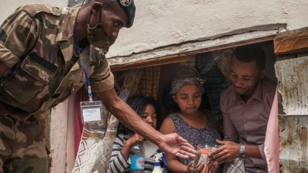 A soldier distributes masks and samples of the Covid-Organics in Antananarivo - April 2020