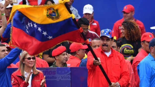Venezuelan President Nicolas Maduro waves a national flag during a gathering with supporters to mark the 20th anniversary of the rise of power of the late Hugo Chavez
