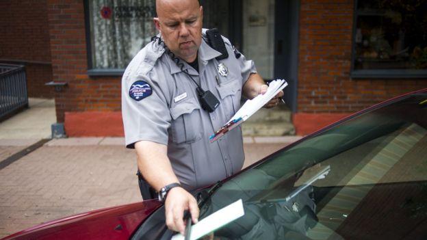 Un policía pone una multa a un auto por estar mal estacionado.