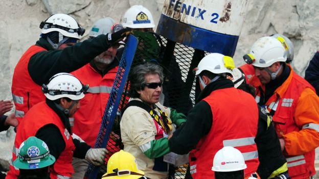 Mario Gómez, uno de los 33 mineros, es ayudado a salir de la cápsula Fénix 2 tras su ascenso a la superficie