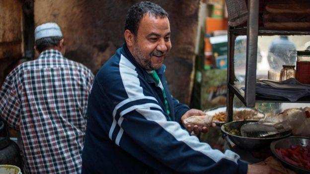 يبدي أمير الذي يقف على عربة طعام في القاهرة ابتسامة تحت شاربه الرمادي أثناء إعداد الفلافل
