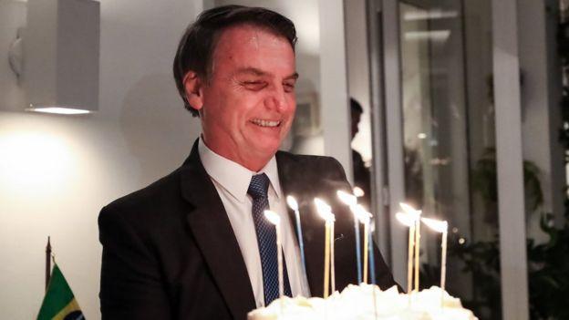 Bolsonaro sorri e segura bolo na comemoração de seu aniversário, em março