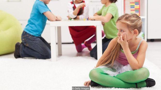 Criança sentada em sala com olhar pensativo, enquanto outras três brincam com jogo de tabuleiro no plano de fundo