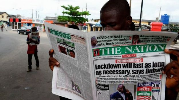 Man reading newspaper in Lagos street