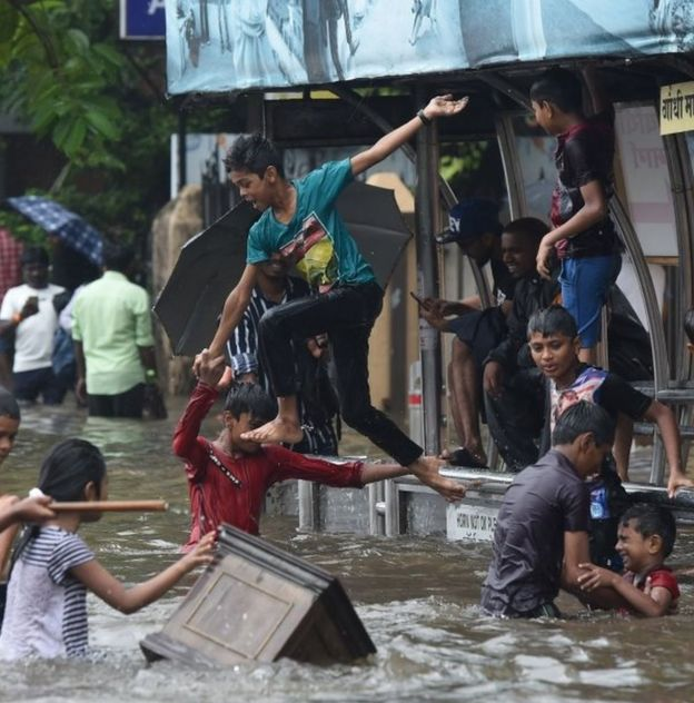 Indian children jump into the water of a flooded street after heavy rain showers in Mumbai on July 1, 2019