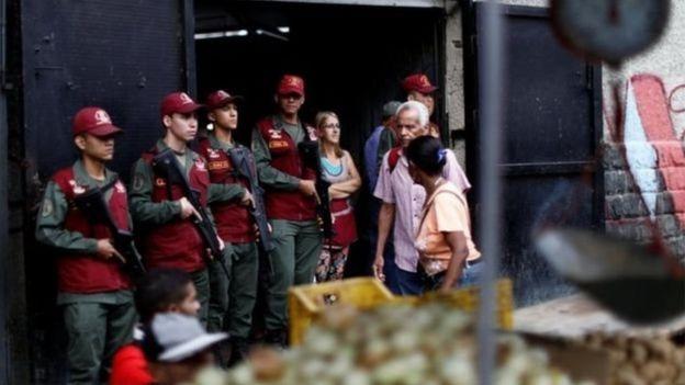 Lính gác có vũ trang đứng canh tại cổng chợ.