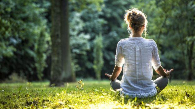 Mujer meditando en un parque.