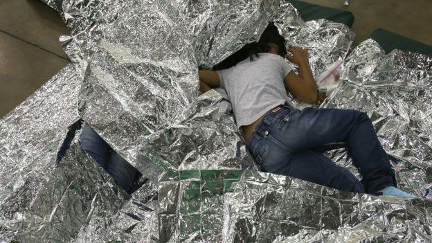 Menina dorme com manta térmica em centro fronteiriço americano, em foto de 2014