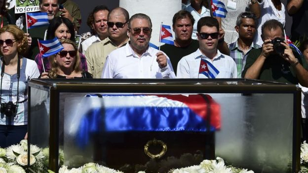 Fidel Ángel Castro Díaz-Balart (C), holds a Cuban national flag as he looks at the urn with the ashes of his father, at the Parque Cespedes in Santiago de Cuba, on December 2, 2016.