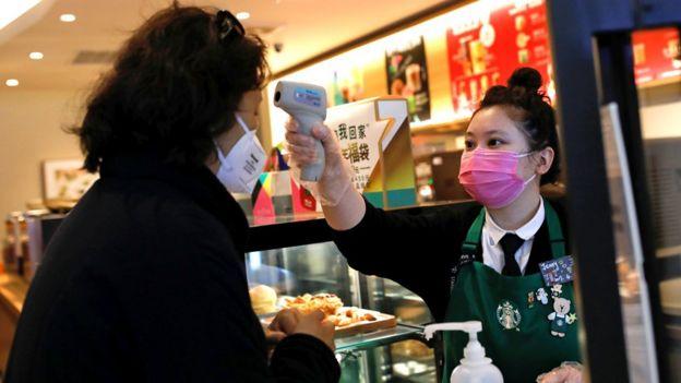 """Работница пекинского """"Старбакса"""" измеряет температуру у посетительницы кофейни"""