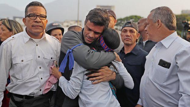 Leopoldo López aparece com uma fita azul no braço e abraçando uma mulher, em meio a apoiadores
