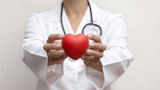 Mulher de jaleco segura um objeto em formato de coração