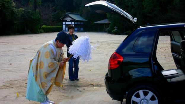 Un sacerdote sintoísta purificando el auto nuevo de una japonesa.