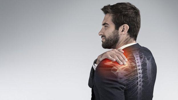 Hombre con traje y dolor en el hombro.