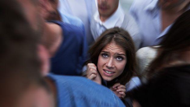 Una mujer visiblemente afectada en medio de una multitud.