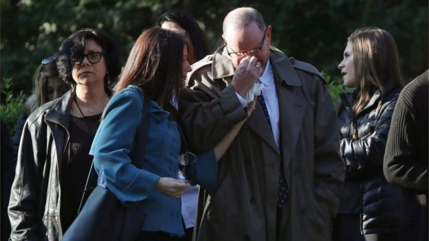 Mourners tear up and hold each other while waiting to pay respects