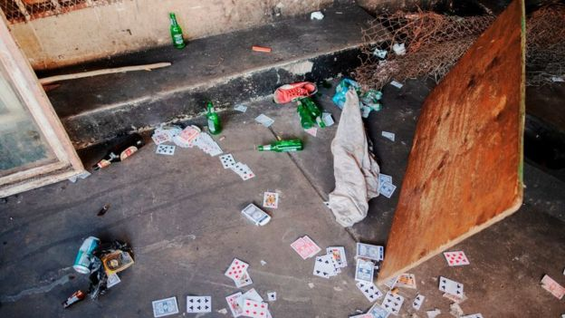 Cards and beer bottles lie on the floor of an informal gambling spot after South African Police Service (SAPS) arrested 8 people because they defied the lockdown rules and the alcohol restriction in Hillbrow, Johannesburg, on March 27, 2020.