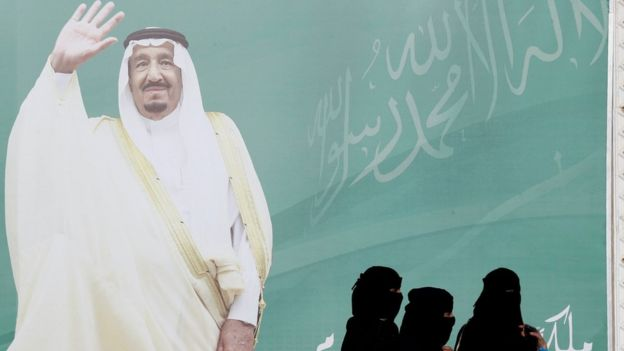 File photo showing women walking past a photo of Saudi Arabia's King Salman in Riyadh (12 February 2018)