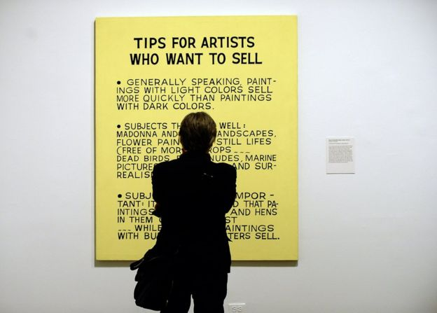 A visitor looks at Baldessari's Tips For Artists Who Want to Sell