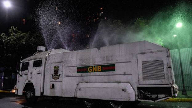 A riot vehicle sprays decontaminant on the streets of Caracas, 30 March