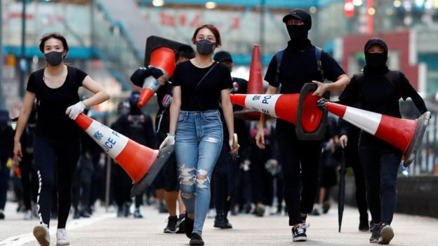 Protesters walk down the road with traffic cones to build a barricade in Causeway Bay, Hong Kong, China November 11, 2019